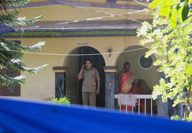 Police officers speak on their mobile phones as they stand on the porch of the house of K M Ashokan,...