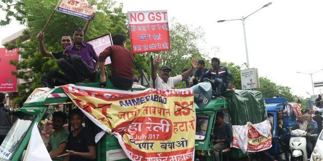 People connected with the textile industry participate in a protest rally against the recently introduced...