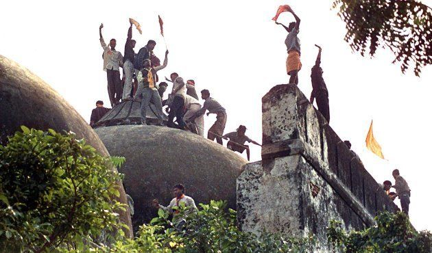 Hindu youths clamour atop the Babri Mosque five hours before the structure was completely