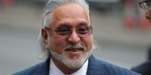 Indian tycoon Vijay Mallya reacts as he waits to re-enter Westminster Magistrates Court in central London...