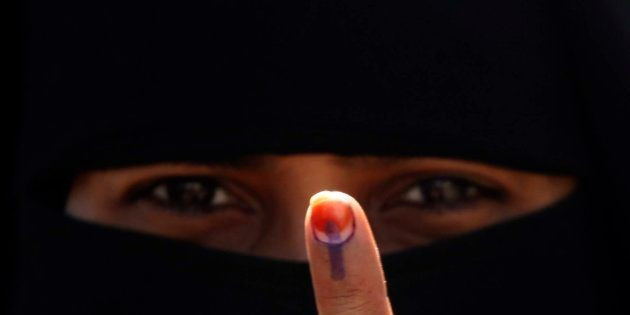 An Indian Muslim woman displays her finger after casting her vote in the first phase polling of Gujarat...
