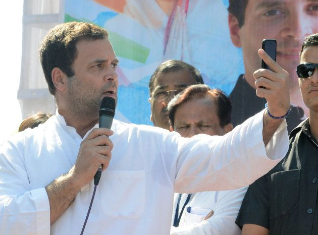 Congress Vice President Rahul Gandhi looks at his mobile phone at rally in Dahegam, some 40km from Ahmedabad,...
