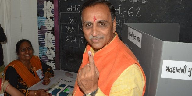 Gujarat state Chief Minister Vijay Rupani shows his inked finger after casting his ballot during the...