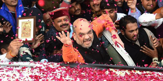 Indian Bharatiya Janata Party (BJP) President Amit Shah (C) shows the victory sign to supporters as he...