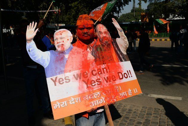 A supporter of India's ruling Bharatiya Janata Party (BJP) holds a placard as he celebrates outside the...