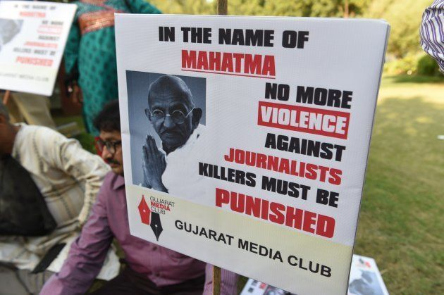 Indian journalist participates in a peace protest near the statue of Mahatma Gandhi at Gandhi Ashram...