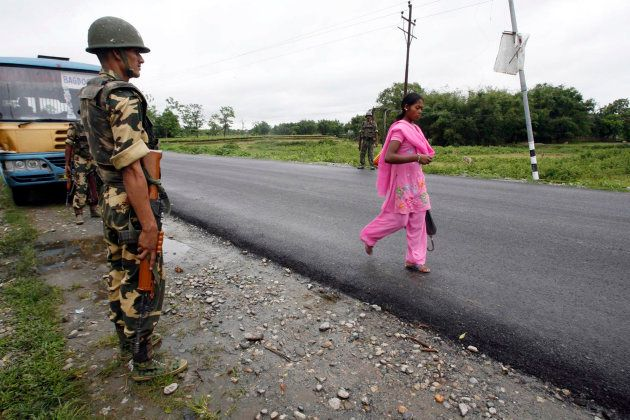 A woman walks past a policeman from the Central Reserve Police Force on a highway during an indefinite...