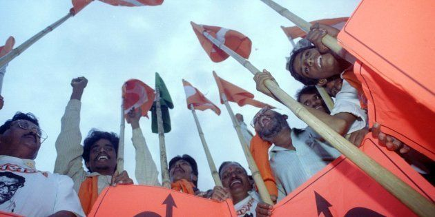 Supporters of the Shiv Sena party brandish their bow and arrow symbols at an election rally in