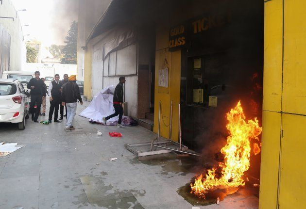 Smoke and fire emerges from a cinema ticket booth after an attack by activists in protest against the...