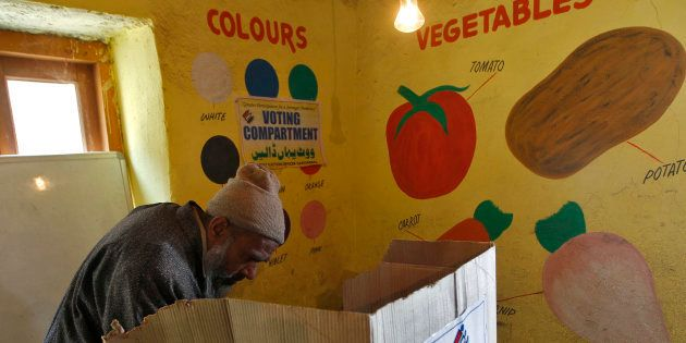 A voter casts his vote at a polling station during the first phase of the Jammu and Kashmir state assembly...