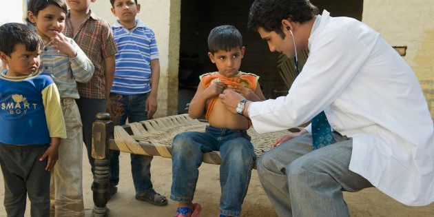 Doctor examining a boy with a stethoscope, Hasanpur, Haryana,