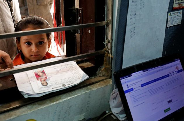 A girl waits for her turn to enrol for the Unique Identification (UID) database system, also known as...
