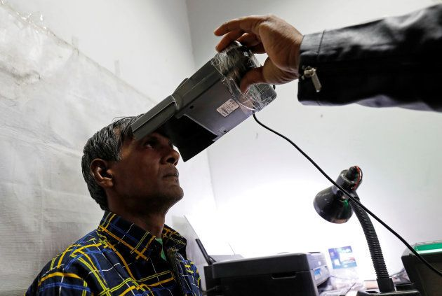 A man goes through the process of eye scanning for the Unique Identification (UID) database system, also...