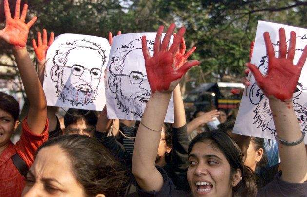 Activists raise their hands covered in red paint during a demonstration against the visit of then Chief...