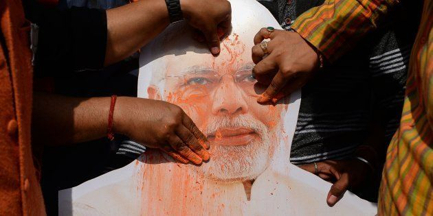 A placard with the image of India's Prime Minister Narendra Modi is covered with colored powder by Indian...