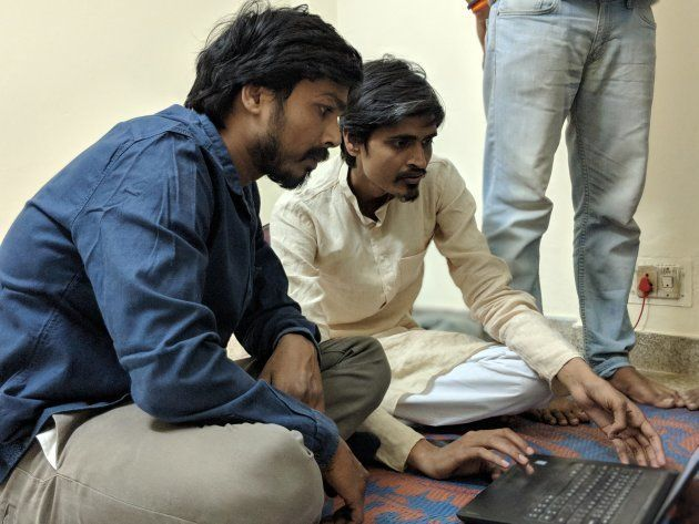 Akhilesh and Vikrant huddle over a laptop as they create the party's