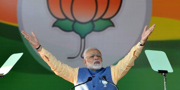 Prime Minister Narendra Modi gestures while addressing a gathering 'Parivarthana Rally' in Bangalore on February 4, 2018.