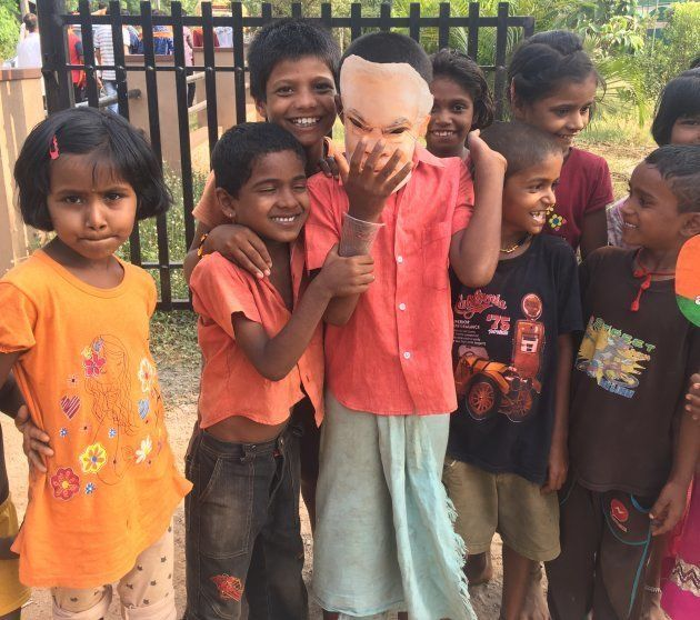 Children play with a Narendra Modi mask near a BJP rally in Udupi on May 1, 2018
