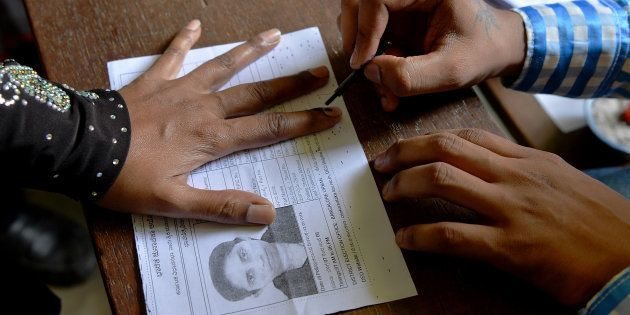 An Indian election official (R) puts indeliable ink on the finger of a voter before she casts her ballot...