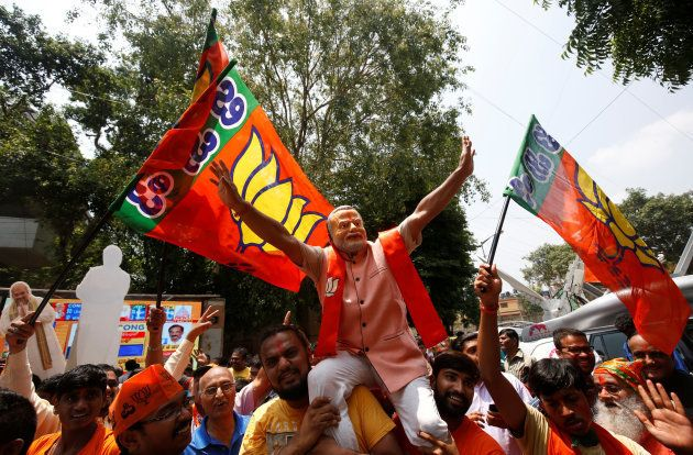 Supporters of India's ruling Bharatiya Janata Party (BJP) celebrate after learning of the initial poll...