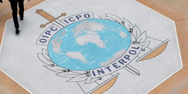 People walk on the Interpol at the international police agency logo in Lyon, central France, Thursday, Nov.8, 2018. (AP Photo/Laurent Cipriani)