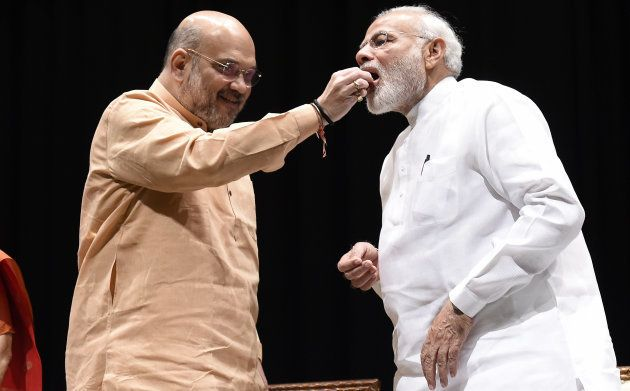 BJP President Amit Shah offers sweets to Prime Minister Narendra Modi during BJP Parliamentary Party meeting on July 31, 2018 in New Delhi.