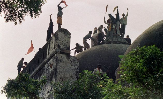 Hindu youths clamour atop the 16th century Muslim Babri Mosque in Ayodhya on December 6,