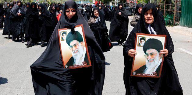 Iranian women carry portraits of former Iranian supreme leaders, Ayatollah Khamenei at a