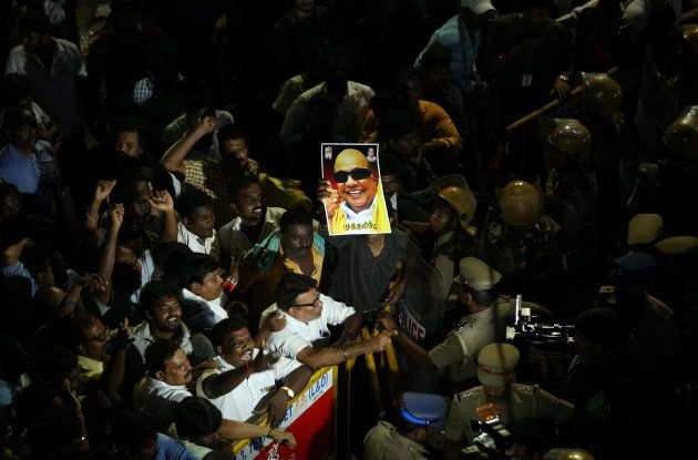 Supporters gather as an ambulance carrying the remains of Indian Tamil leader M. Karunanidhi leaves the...
