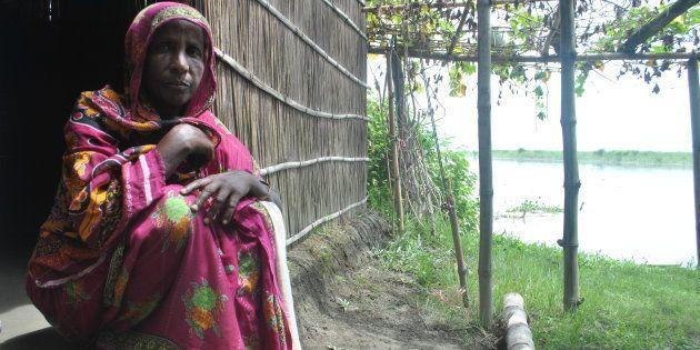 Rabiya Khatun sits in her hut by the Brahmaputra