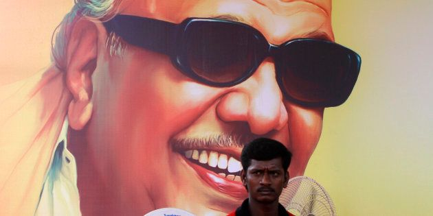 A supporter of Dravida Munnetra Kazhagam (DMK) party sits in front of the poster of party chief M. Karunanidhi...