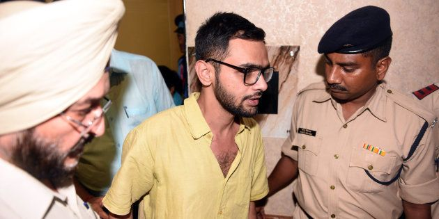 Delhi police officials with JNU student Umar Khalid who escaped unhurt after an unidentified man shot...