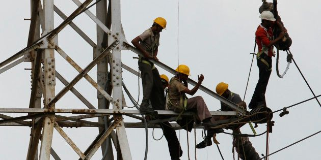 Linemen set up high tension power lines on the outskirts of