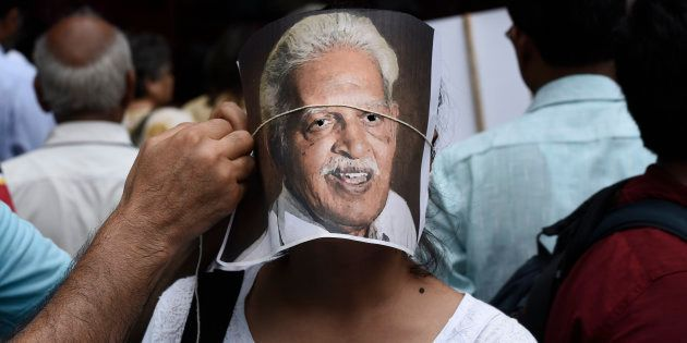 NEW DELHI, INDIA - AUGUST 30: A protester adjusts a portrait of poet Varavara Rao on the face of another...