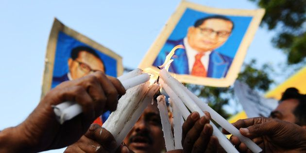 REPRESENTATIONAL IMAGE. Indian activists hold candles and portraits of 20th century Indian social reformer...