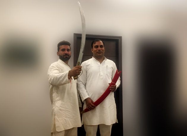 Hariom Sisodia and Amit Jani pose with a sword in Noida on September 26,