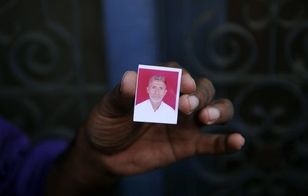 A relative holds a photograph of slain villager Mohammad Akhlaq at his home in the village of