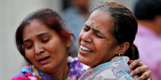 Women mourn the death of a relative after a commuter train traveling at high speed ran through a crowd...