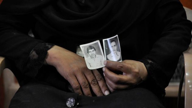 A woman shows picture of her relatives who were killed in the 1987 Hashimpura massacre during a press...