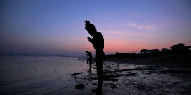 A Hindu holy man offers prayers by the Saryu River on the eve of the anniversary of the Babri mosque...