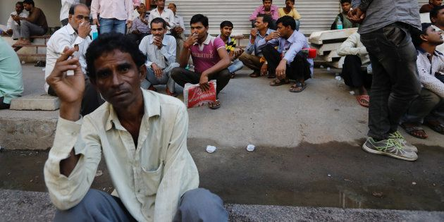 Tradespeople sit on the side of a road as they wait to get hired for work in Mumbai, India, November...