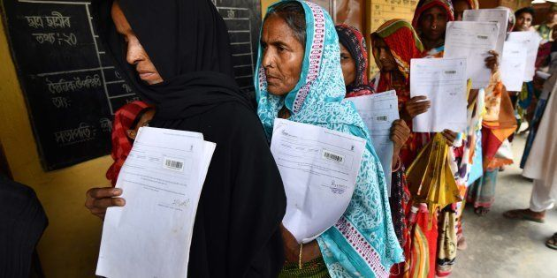 Residents of Burgaon village in Morigaon, Assam, hold their documents as they stand in a queue to check...