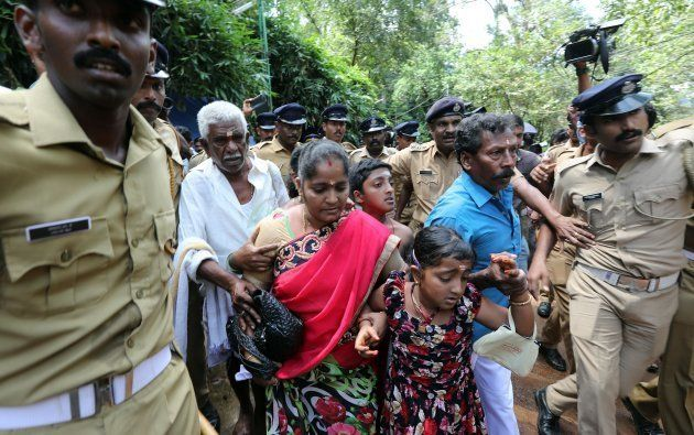 Police escort Andhra Pradesh resident Madhavi and her family members after she was heckled by protesters...