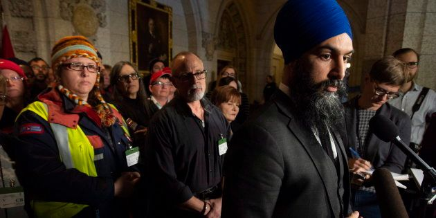 Surrounded by members of Canada Post NDP leader Jagmeet Singh listens to a question from the media about...