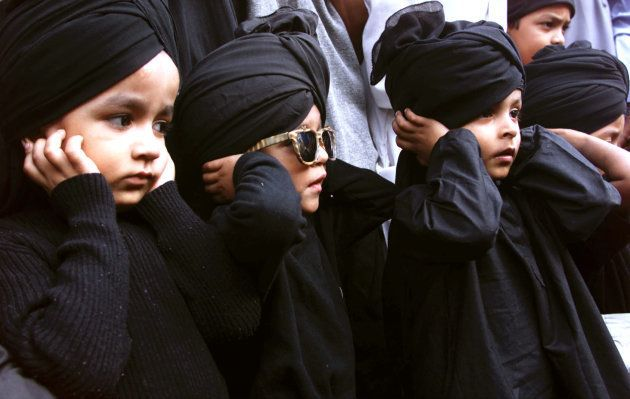 Children from the Muslim religious group 'Raza Academy' cover their ears as a part of a prayer ritual...