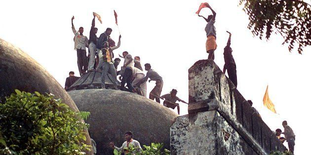 Hindu youths clamour atop the 16th century Babri Mosque on 6 December