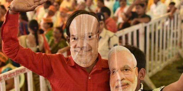 BJP workers wearing masks of party president Amit Shah and Prime Minister Narendra Modi in