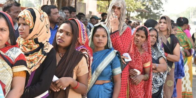 Voters stand in a queue to cast their votes in Madhya
