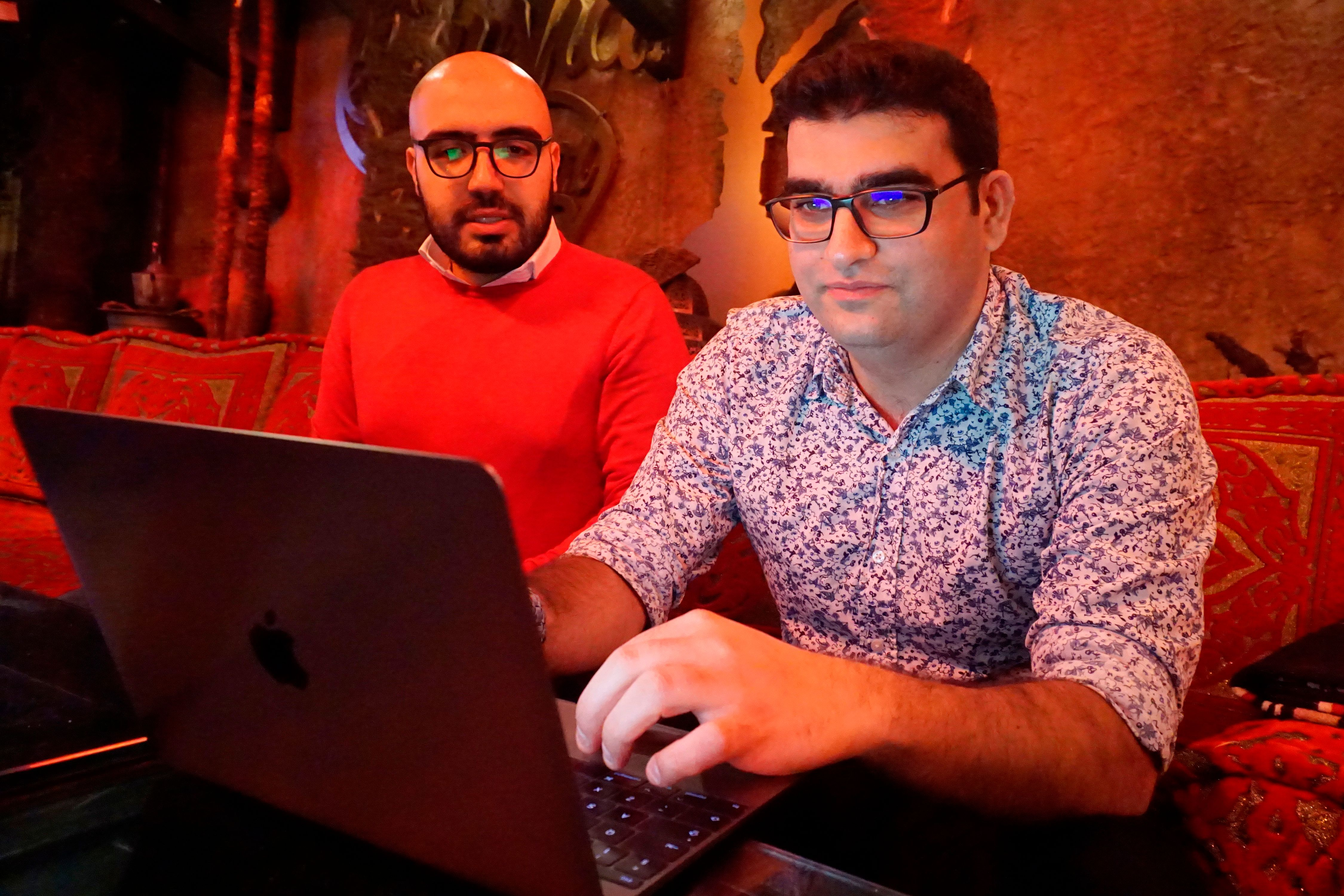 Certfa researchers Nariman Gharib, left, and Amin Sabeti look at a computer at a cafe in London on Friday, Dec. 7, 2018. The Associated Press drew on data gathered by the London-based cybersecurity group Certfa to track how a hacking group often nicknamed Charming Kitten spent the past month trying to break into the private emails of more than a dozen U.S. Treasury officials. Also on the hackers' hit list: high-profile defenders, detractors and enforcers of the nuclear deal struck between Washington and Tehran, as well as Arab atomic scientists, Iranian civil society figures and D.C. think tank employees. (AP Photo/Raphael Satter)