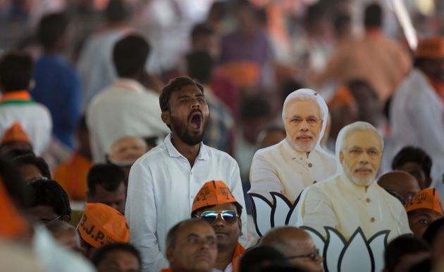 A Bharatiya Janata Party supporter yawns during an election campaign rally addressed by Prime Minister...